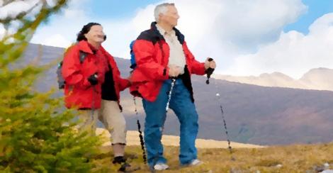 cute seniorcouple hiking in an autumn mountainlandscape
